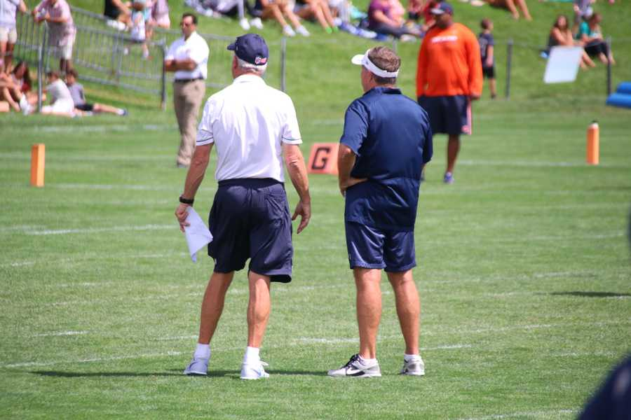 Bears Head Coach John Fox stands next to Patriots head coach Bill Belichick as they watch their teams on the field.
