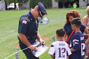 The Abington Police Chief signs an autograph for Patriots fans at practice Wednesday.