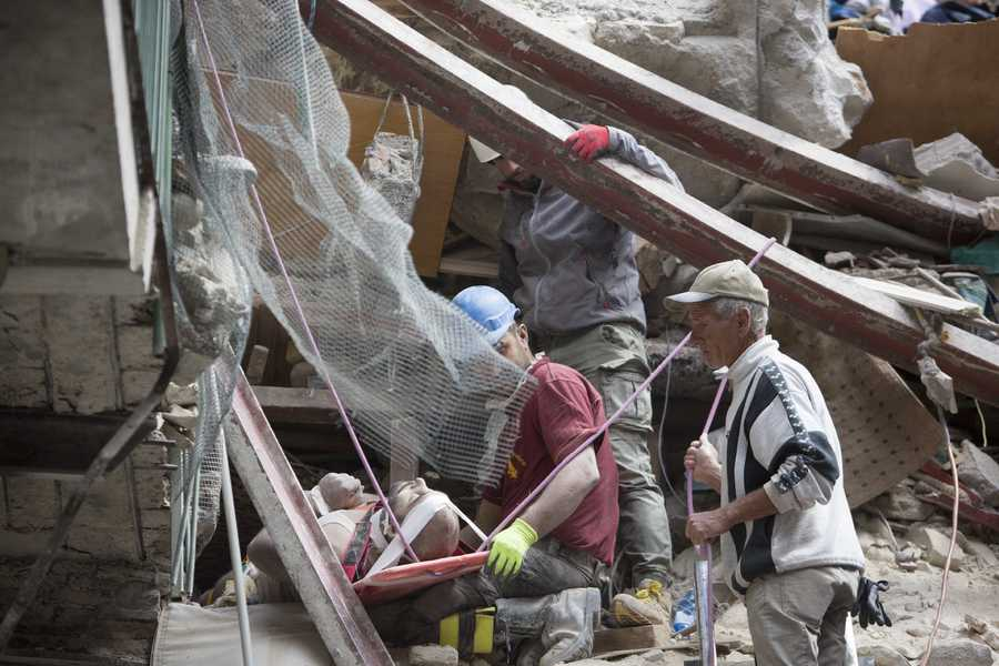 An injured man is rescued from a collapsed building following an earthquake in Amatrice, central Italy, Wednesday, Aug. 24, 2016. The magnitude 6 quake struck at 3:36 a.m. and was felt across a broad swath of central Italy, including Rome where residents of the capital felt a long swaying followed by aftershocks.