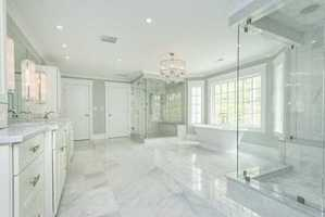 Spectacular fireplaced master suite features gorgeous bath, 2 individual water closets.