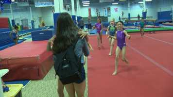 Young gymnasts at Brestyan's American Gymnastic Club run to greet Aly Raisman on Friday.