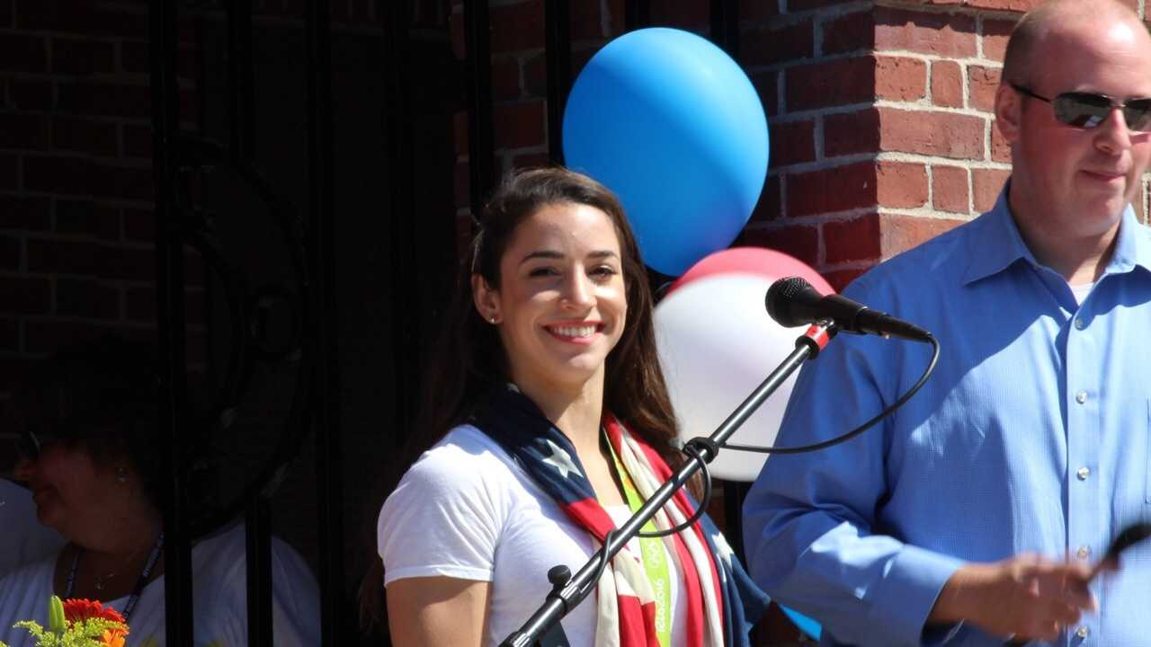 Raisman smiles at the audience gathered in Needham.