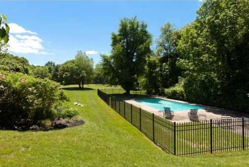The privately sited in-ground pool is set in a corner of the landscaped grounds.