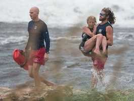 A man trying to help her was also knocked into the water, but both were rescued from the rough surf.