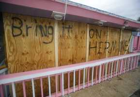A hand painted sign on a boarded up bar is seen as Hurricane Hermine nears the Florida coast, Thursday, Sept. 1, 2016, in Cedar Key, Fla. ?Hurricane Hermine gained new strength Thursday evening and roared ever closer to Florida's Gulf Coast, where rough surf began smashing against docks and boathouses and people braced for the first direct hit on the state from a hurricane in over a decade. ?(AP Photo/John Raoux)