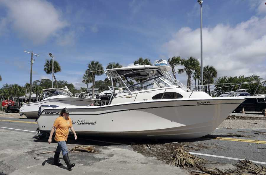 A woman walks past pleasure boats that were washed into Riverside Dr., when Hurricane Hermine came ashore early Friday, Sept. 2, 2016, in Steinhatchee, Fla. Hermine was downgraded to a tropical storm after it made landfall, as it moves over Georgia, but the U.S. National Hurricane Center says winds are increasing along the Southeast coast and flooding rains continue.(AP Photo/Chris O'Meara)