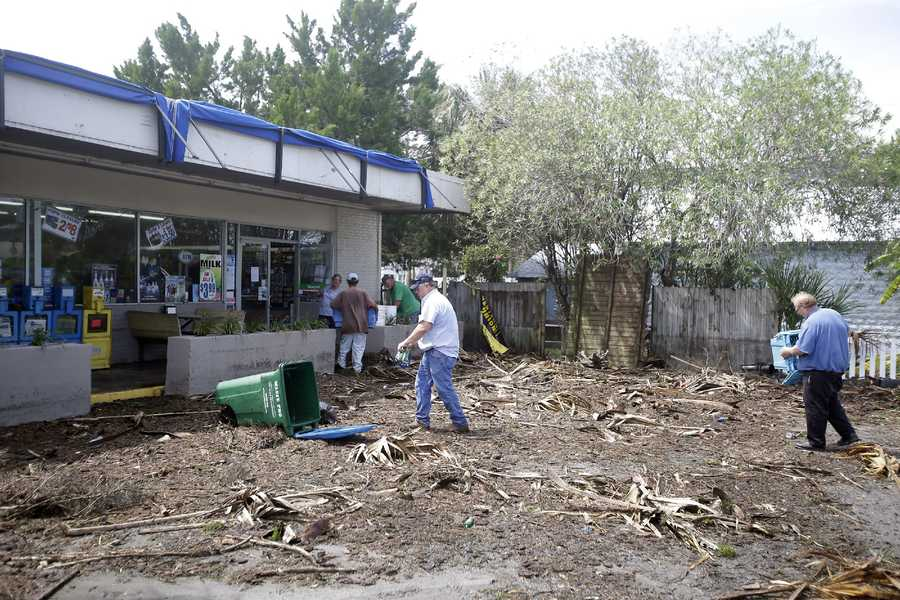 Workers clean up debris, caused by Hurricane Hermine, in the parking lot in front of convenience store, Friday, Sept. 2, 2016, in Cedar Key, Fla. Hermine was downgraded to a tropical storm after it made landfall. (AP Photo/John Raoux)