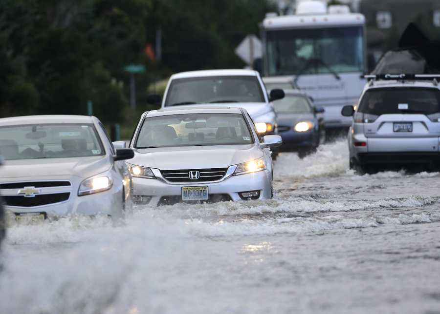 Cars drive on the flooded NC Hwy 12 in Rodanthe, N.C., Saturday, Sept. 3, 2016 after Tropical Storm Hermine passed the Outer Banks. The storm is expected to dump several inches of rain in parts of coastal Virginia, Maryland, Delaware, New Jersey and New York as the Labor Day weekend continues. (AP Photo/Tom Copeland)