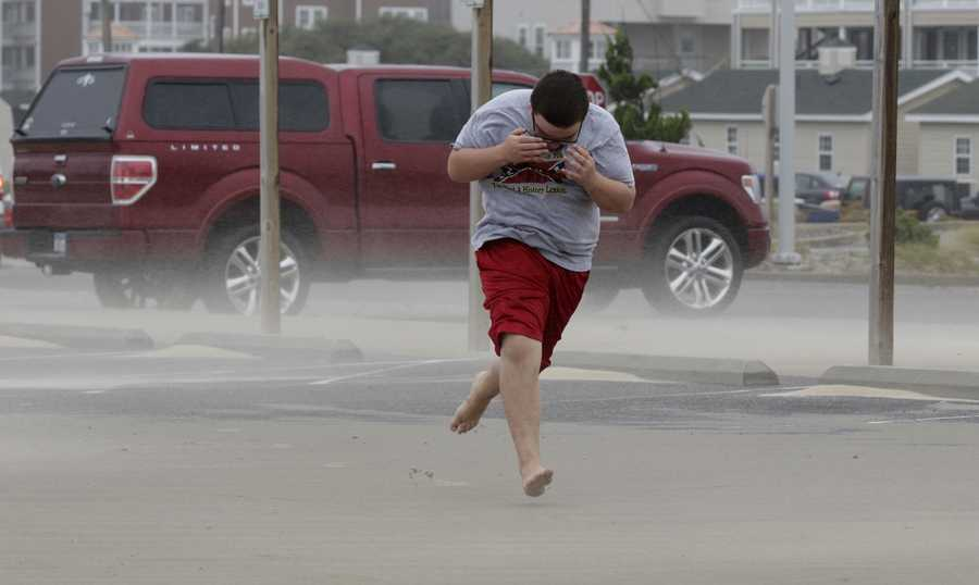 Eli White covers his face from the blowing sand in Nags Head, N.C., Saturday, Sept. 3, 2016 as the tail of Tropical Storm Hermine passes the Outer Banks. Hermine lost hurricane strength over land but was intensifying Saturday along the Atlantic Coast, threatening heavy rain, wind and storm surges on its northward march. (AP Photo/Tom Copeland)