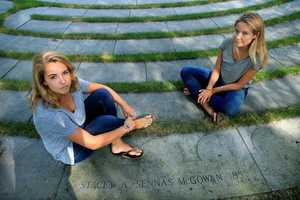 Sisters Ryan, left, and Casey McGowan sit beside the stone honoring their mother on the Boston College campus.