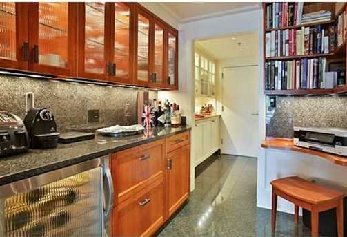 Custom kitchen with cherry wood and Pilkington scalloped glass cabinetry, granite counters & floors and extra large pantry, flows into gracious living/dining area with sliders to one of three 16' x 5' private balconies.