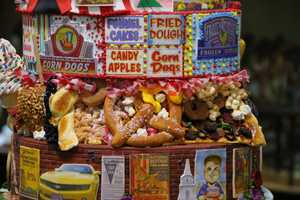 Each tier represents a decade in The Big E's history. Two of those tiers are filled with lifelike, to scale, foods, unique to The Big E like such as the turkey leg and the Big E Cream Puff.