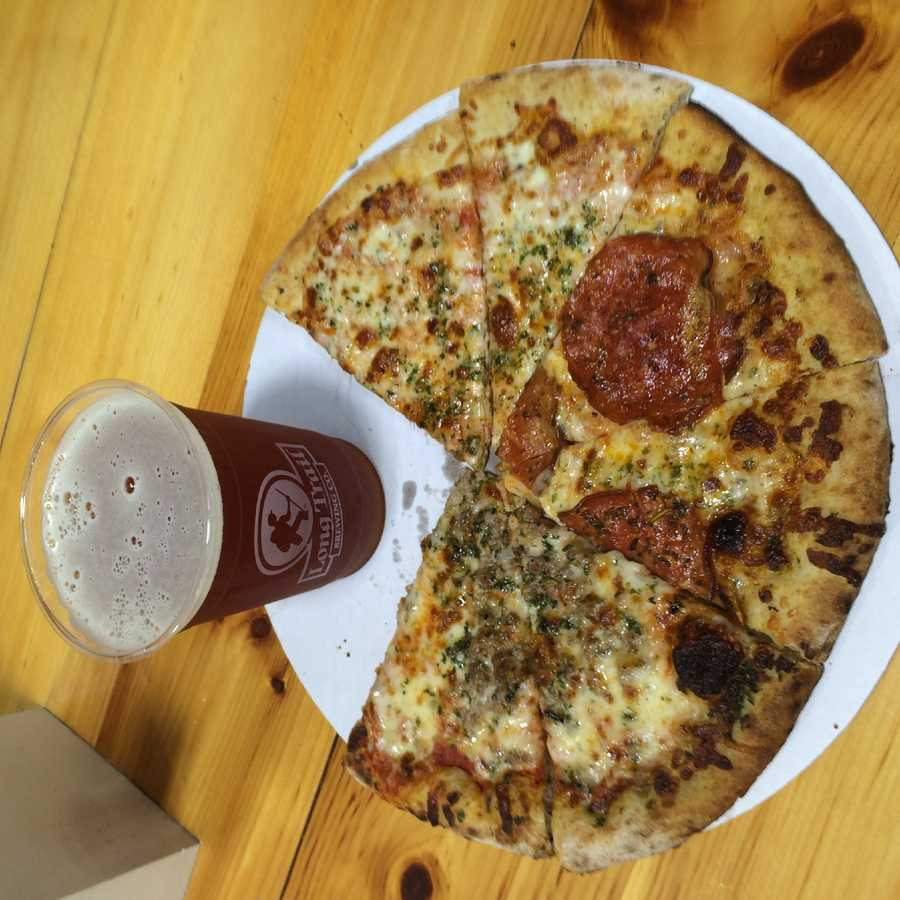 Vermont Flatbread Company cheese, pepperoni and maple sausage flatbread pizza slices and an Otter Creek Octoberfest from the Vermont State Building.