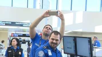 A Make-A-Wish rep and a TSA worker smile as they look on.