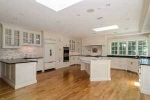 Gracious eat-in fireplaced chef's kitchen with large island, Wolf range and French doors to patio.