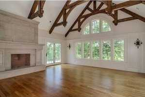 Architecturally significant vaulted-ceiling great room with soaring custom trusses and stately stone fireplace.