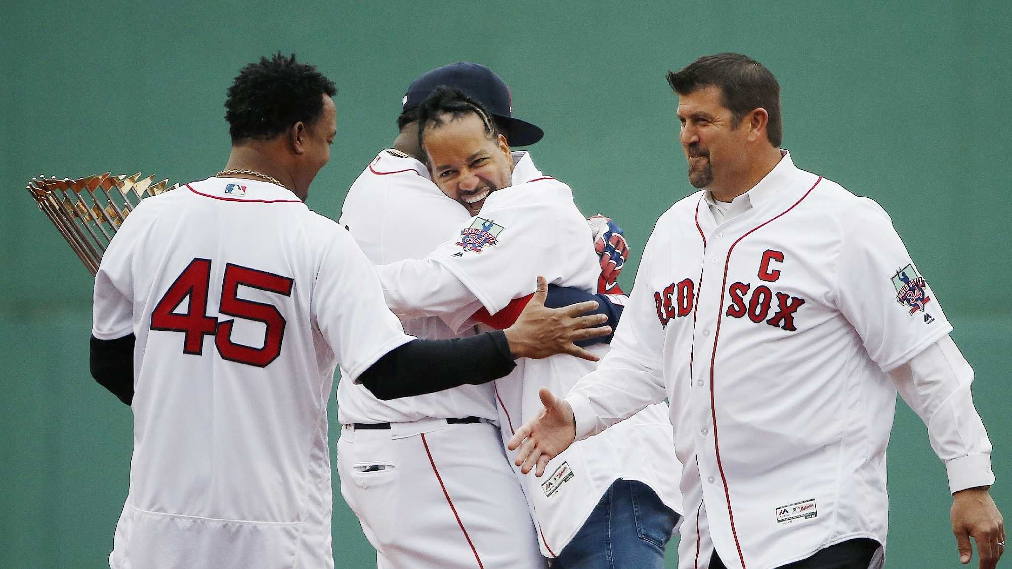 Boston Red Sox's David Ortiz, center left, hugs former teammate Manny Ramirez, center right, behind former teammates Pedro Martinez, left, and Jason Varitek during a ceremony before a baseball game against the Toronto Blue Jays in Boston, Sunday, Oct. 2, 2016.