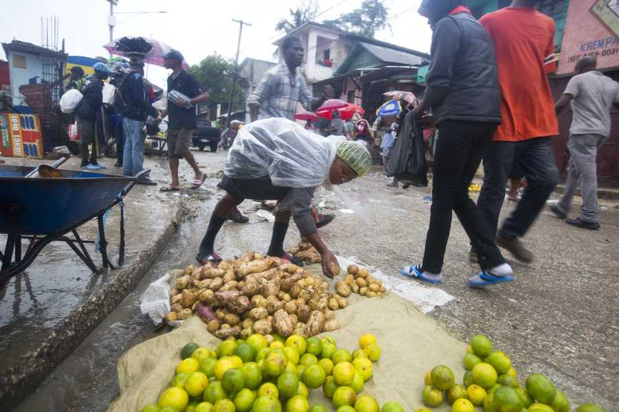 A food vender puts out her goods for sale during a light triggered by Hurricane Matthew in Port-au-Prince, Haiti