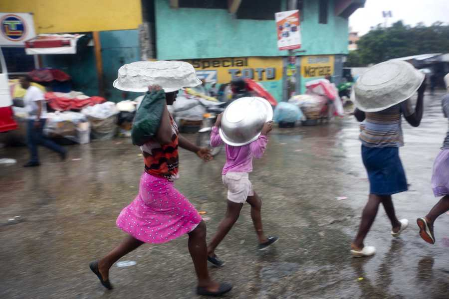 Women cover their heads with pans as they walk in a light rain brought by Hurricane Matthew in Port-au-Prince, Haiti.