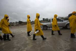 Civil protection workers walk in to evacuate residents from the Grise river area, prior the arrival of Hurricane Matthew
