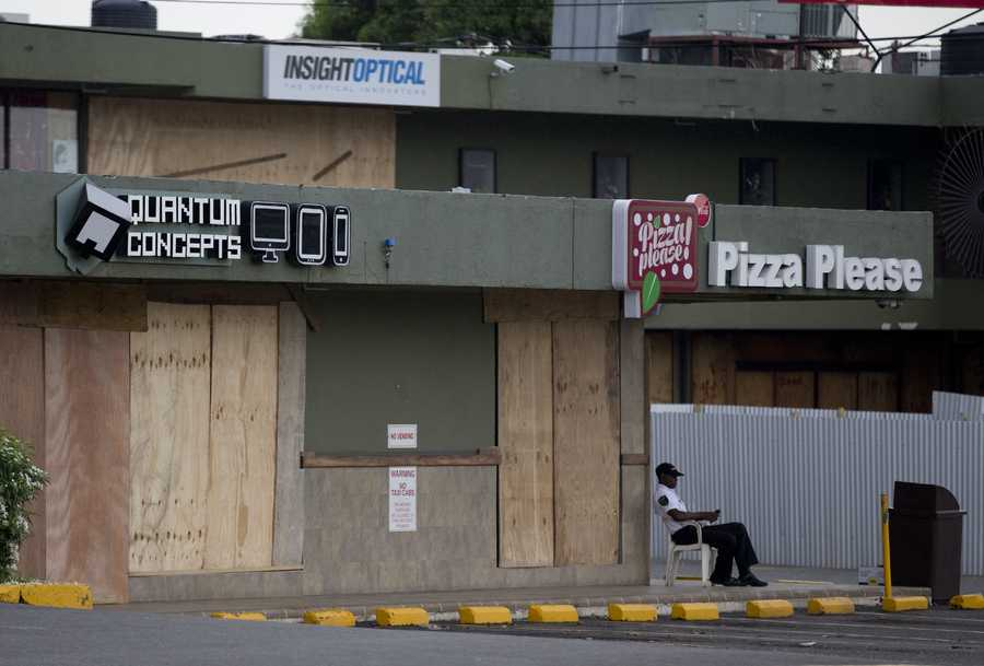 A security guard sits next to a several stores that had their windows covered with plywood in preparation for the arrival of Hurricane Matthew in Kingston, Jamaica