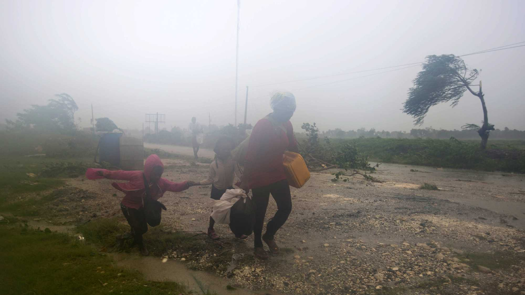 Residents head to a shelter in Leogane, Haiti, Tuesday, Oct. 4, 2016. Matthew slammed into Haiti's southwestern tip with howling, 145 mph winds Tuesday, tearing off roofs in the poor and largely rural area, uprooting trees and leaving rivers bloated and choked with debris.