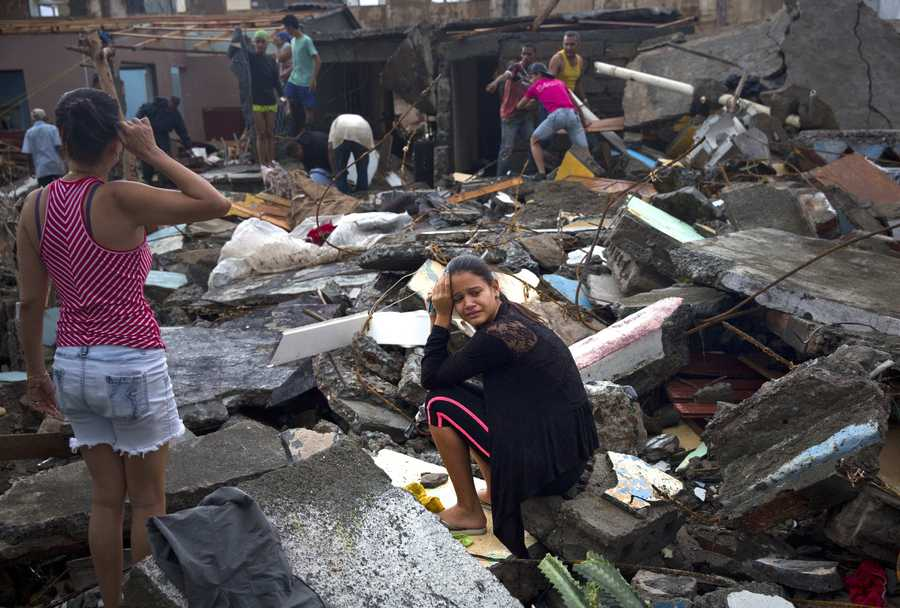 A woman cries amid the rubble of her home, destroyed by Hurricane Matthew in Baracoa, Cuba, Wednesday, Oct. 5, 2016. The hurricane rolled across the sparsely populated tip of Cuba overnight, destroying dozens of homes in Cuba's easternmost city, Baracoa, leaving hundreds of others damaged. (AP Photo/Ramon Espinosa)