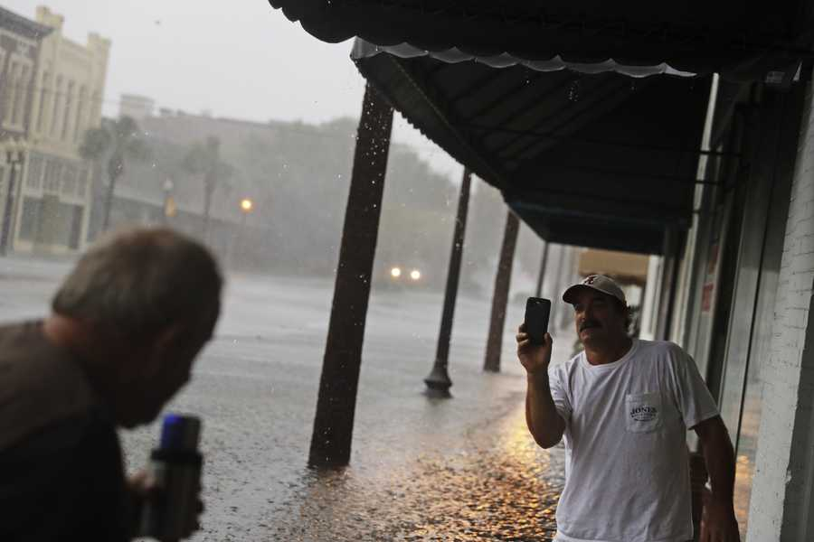 Keith Paseur, right, and Pat Barlow survey a flooded street from Hurricane Matthew as they check on a neighbor riding out the storm in their store in downtown Brunswick, Ga., Friday, Oct. 7, 2016.