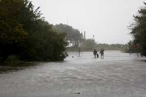 People walk down Station 30 with their dog as Hurricane Matthew hits Sullivan's Island, S.C., Saturday, October 8, 2016. Matthew is continuing its march along the Atlantic coast, lashing two of the South's most historic cities and some of its most popular resort islands with heavy rain and stiff winds.