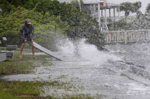 Resident Kelly Fitz pulls dislodges lumber from an overflowing seawall in Wrightsville Beach, N.C., Saturday, Oct. 8, 2016 as Hurricane Matthew moves into the Carolinas.