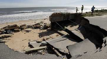 A missing section of highway A1A that was washed out by Hurricane Matthew is photographed by officials and media, Saturday, Oct. 8, 2016, in Flagler Beach, Fla. The damage from Matthew caused beach erosion, washed out some roads and knocked out power for more than 1 million customers in several coastal counties.