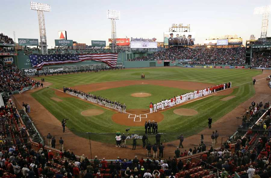 The Cleveland Indians, left, and the Boston Red Sox line the foul lines during the national anthem before Game 3 of baseball's American League Division Series, Monday, Oct. 10, 2016, in Boston.