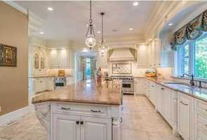 The gourmet kitchen features a breakfast room that leads to an outdoor patio, perfect for entertaining family and friends.