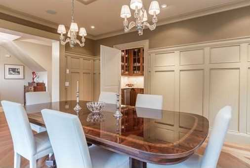 The open foyer leads to a formal living room with gas fireplace and a dining room that connects to a butler's pantry complete with sink, custom cabinetry, wine fridge, ice maker and dishwasher.