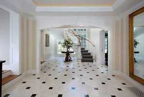 A sun drenched foyer with dramatic curving staircase.