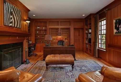 A cherry paneled library with fireplace.