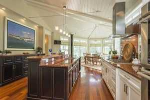 The home has a chef's kitchen, breakfast room with gas fireplace, home office, vaulted ceilings, built-in cabinets, walls of windows and hardwood floors throughout and a no expense spared level of attention to detail.