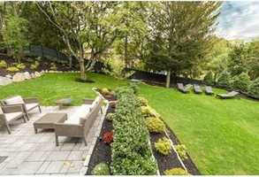 Fenced lush grounds with stone retaining walls, mature trees, spacious Patio, and ideal space for a future swimming pool.