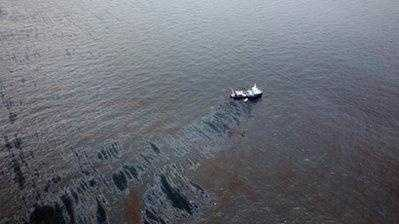A pool of oil floats in the Gulf of Mexico more than 50 miles southeast of Venice, La., as a boat with booms tries to contain the spill from the Deepwater Horizon rig. (2010)