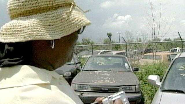 A woman surveys a car at one of last year's abandoned vehicle auctions.