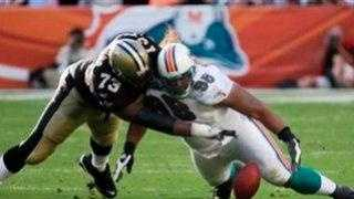 Saints guard Jahri Evans, left, and Miami Dolphins defensive end Paul Soliai battle for a loose ball.