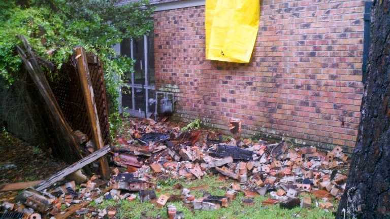 Scattered bricks illustrate the power of a lightning bolt that struck a home in Covington