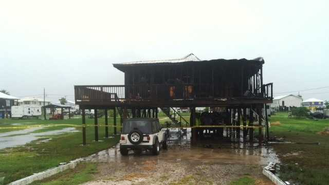 The charred remains of a burned-out Grand Isle home stand near Hwy. 1.