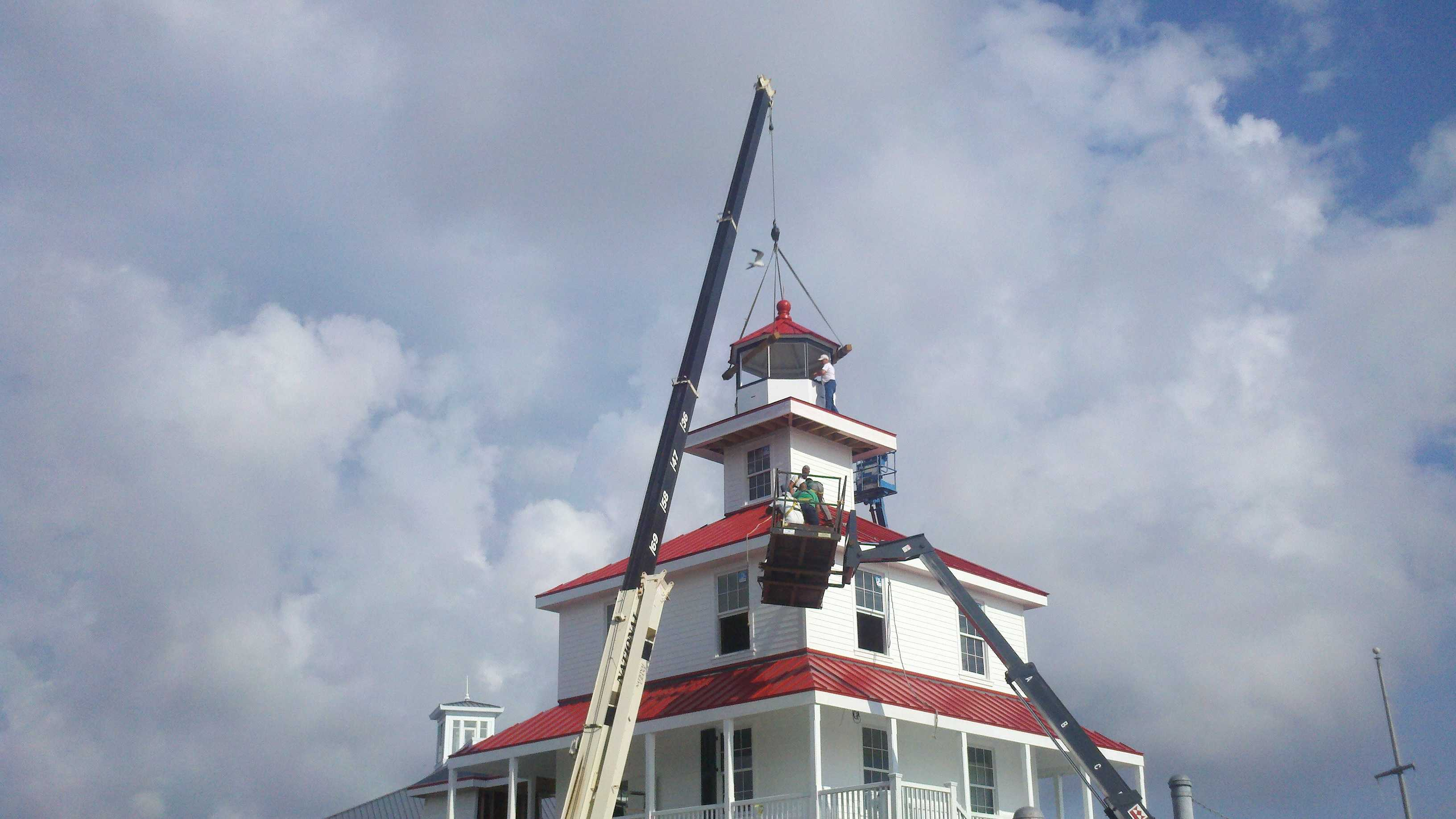 Crews hoist the new cupola on top of the New Canal Lighthouse