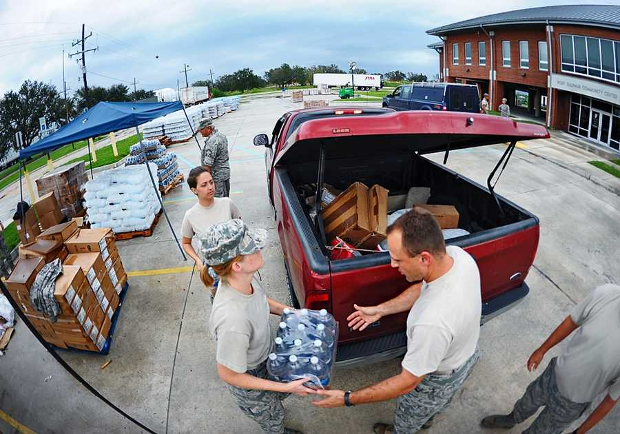 PORT SULPHUR, La. - Louisiana Air National Guardsmen, Senior Airman Hunni B. Bolton and Senior Airman Gary Martin, both of the 259th Air Traffic Control Squadron, load commodities into the back of a resident's vehicle, Sept. 5, 2012. The LANG has conducted more than 260 emergency response missions since Hurricane Isaac operations began.