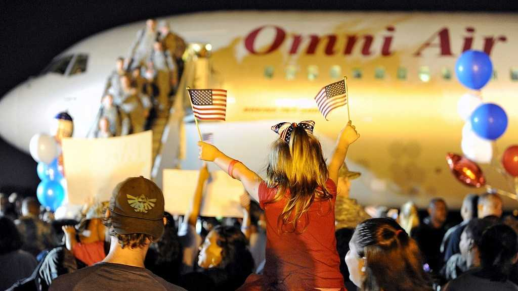 A little girl displays her patriotism as an excited crowd cheers returning Louisiana National Guard Airmen of the 159th Fighter Wing off the plane during a welcome-home event at the Naval Air Station, Joint Reserve Base, New Orleans in Belle Chasse, La., Oct. 11, 2012.