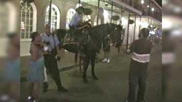 Again in the video, Johnson walks up to New Orleans Police Department mounted patrol officers and asks for directions while on Bourbon Street sometime in 2009.