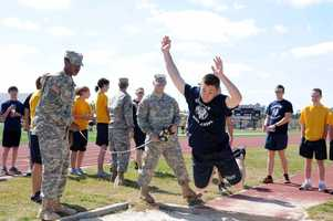 JROTC cadet in mid air on a long jump attempt.