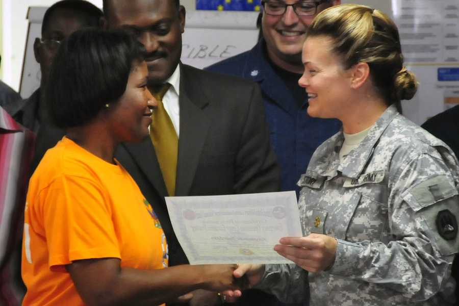 PORT-AU-PRINCE, Haiti - Maj. Michelle R. Story, of Diamondhead, Miss., commander of the Louisiana National Guard's military engagement team, awards a completion certificate to Raymonde Jourdain, technical coordinator of the Central Department, for her participation in the emergency operations center executive training at the Haitian Directorate of Civil Protection national emergency operations center in Port-au-Prince, Haiti, May 13, 2013. The LANG's MET is on a four-week mission to train Haitian government officials on effective emergency response management and emergency supplies storage and distribution.