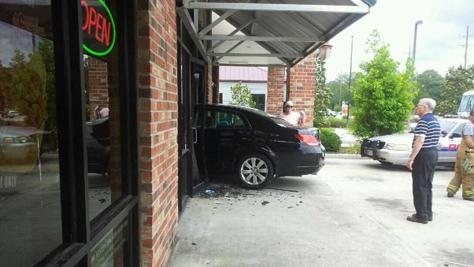 A vehicle protrudes from a strip mall in Covington after the driver apparently lost control.